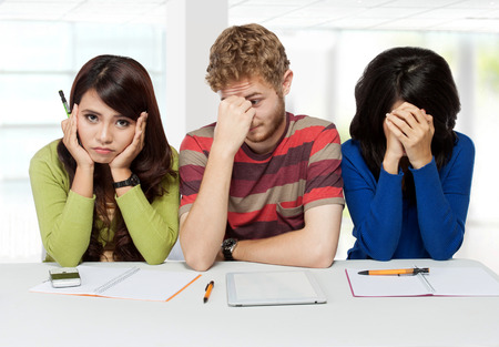 exam room: A portrait of three stress young students sitting together after failing exam
