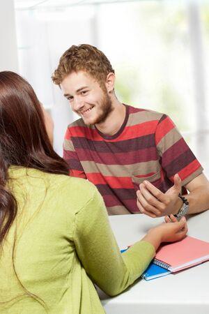 estudiantes adultos: Un retrato de dos j�venes estudiantes universitarios que estudian juntos en la clase sentados en un escritorio Foto de archivo