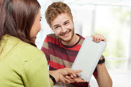 estudiantes adultos: Un retrato de dos j�venes estudiantes universitarios que estudian juntos en la clase sentados en un escritorio. explicando que usa la tableta. espacio de tableta de pantalla en blanco para su dise�o Foto de archivo