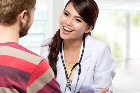 consulta médica: Un retrato de un médico sonriente que da una consulta a un paciente en su consultorio médico Foto de archivo