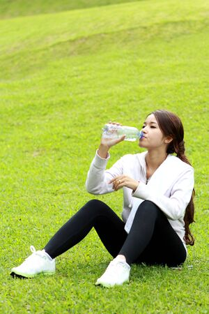 get a workout: portrait of sporty woman sitting on the grass and get refreshment after workout with copyspace