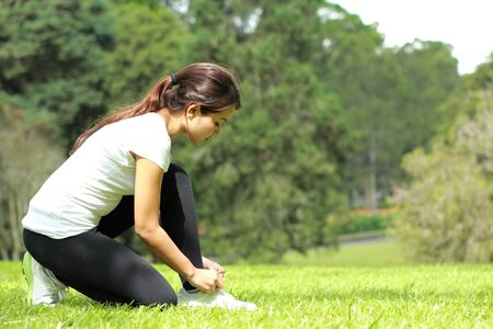 shoelace: portrait of sporty woman tying her shoelace during workout at park with copyspace Stock Photo
