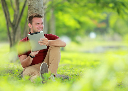 enjoy space: portrait of college student enjoy sitting under the tree while playing a tablet with copy space Stock Photo