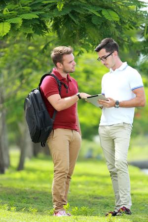 hombre rojo: retrato de un estudiante universitario de explicar un tema a su amigo en el parque de la universidad Foto de archivo