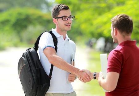 vysoká škola: portrét pohledný student s brýlemi setkat s jeho přítelem v College Park a potřást rukou