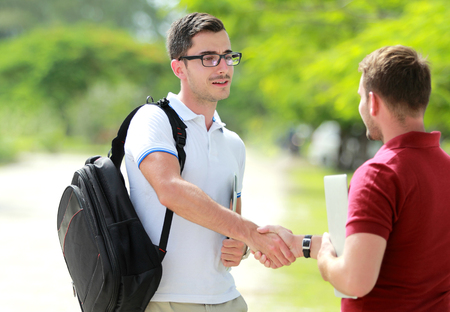 students fun: portrait of handsome college student with glasses meet his friend at college park and shake hands Stock Photo