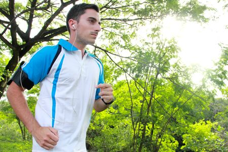 earphone: portrait of sporty fit young man jogging while listening music on smarthphone