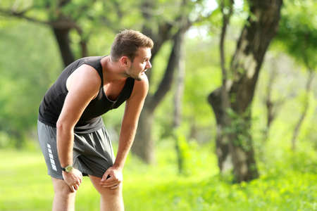 taking a break: portrait of male runner taking a break after a tired running with copy space