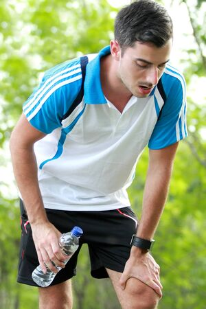 running water: portrait of sporty male runner taking a break after tired running while holding a bottle of mineral water Stock Photo