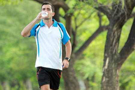 portrait of young sporty man walking while drinking a mineral water for refreshment photo