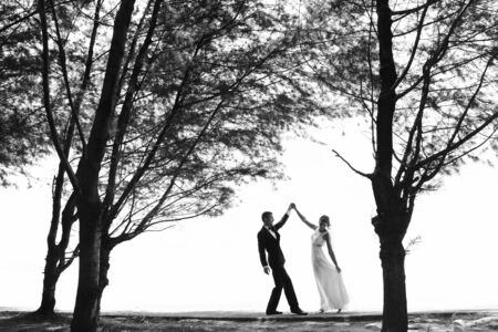 white wedding: black and white photo of wedding couple dancing under the tree