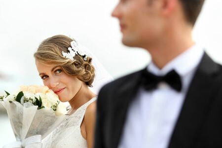 portrait of bride holding a bouquet while looking at her groom photo