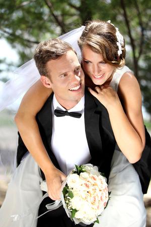 portrait of gentleman groom pickaback his beautiful bride photo