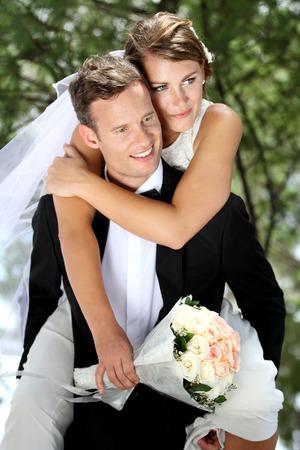 portrait of gentleman groom pickaback his beautiful bride Foto de archivo