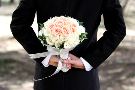 hand holding flower: groom holding a bouquet behind his back