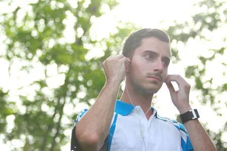 portrait of sporty young man adjusting his earphone during jogging with copy space photo