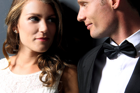 close up portrait of beautiful bride and handsome groom looking each other photo