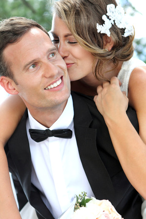 wedding hairstyle: portrait of beautiful bride kissing her handsome groom Stock Photo