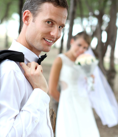 portrait of handsome groom smiling and looking at camera with his background photo