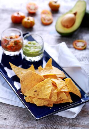 mexican food: portrait of light and crispy corn chips served with salsa and guacamole at blue plate