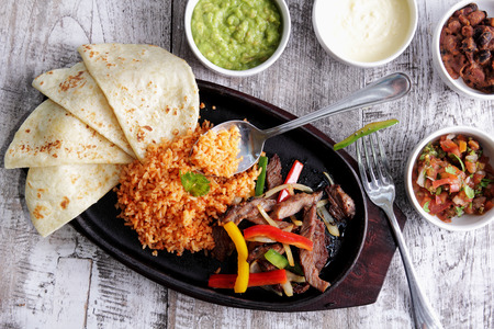 serving food: portrait of mexican cuisine fajitas served with soft flour tortillas, rice, bean chili, salsa, guacamole and sour cream Stock Photo