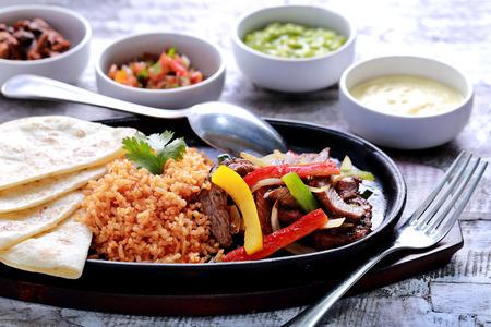 Mexicaanse rundvlees fajitas geserveerd met rijst, zachte tortilla's op hete plaat en vier verschillende sauzen Stockfoto