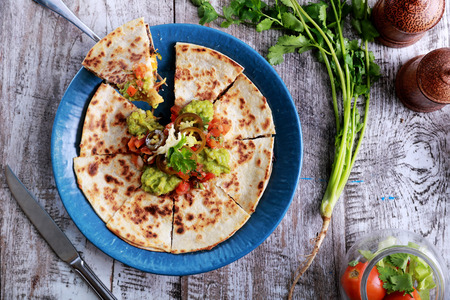 mexican food: top view mexican cuisine quesadilla served at blue plate with guacamole, salsa and jalapenos Stock Photo