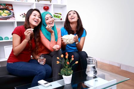 roommates: portrait of three beautiful women laughing together watching funny movie Stock Photo