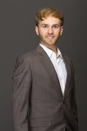 entrepeneur: portrait of handsome young businessman smiling wearing casual suit isolated on grey Stock Photo