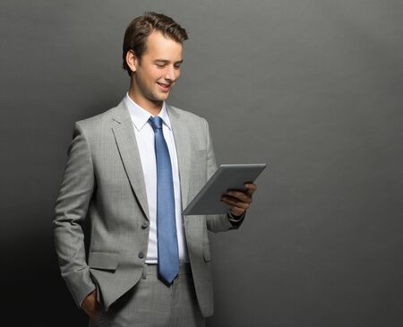 portrait of young businessman holding a tablet and the other hand in pocket isolated on grey photo