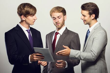 entrepeneur: portrait of a group of businessman discussing about their ideas isolated on grey
