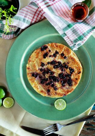 maple syrup: top view of blueberry pancake on green plate served with maple syrup