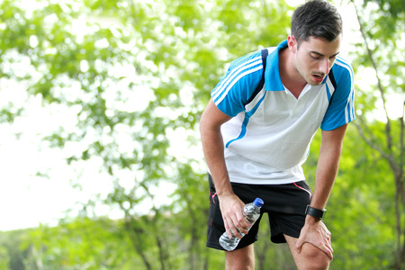 portrait of sporty male runner taking a break after tired running while holding a bottle of mineral water with copy space photo