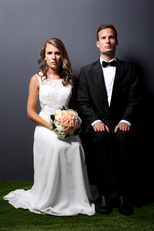 groom and bride: portrait of young newlywed couple sitting on a chair with dark background