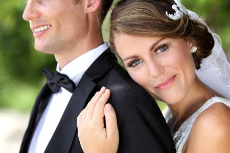 portrait of beautiful bride smiling while embracing her groom from behind Stock Photo