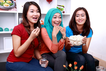watching movie: portrait of three beautiful young women look excited when watching a movie