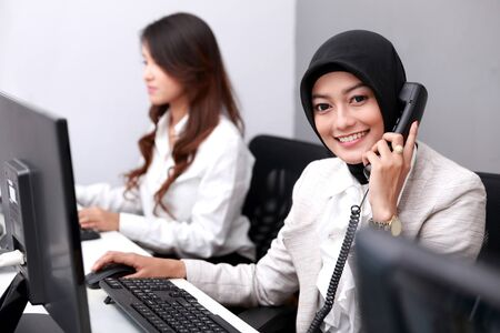 phone operator: portrait of beautiful businesswoman smiling while answering the telephone at office