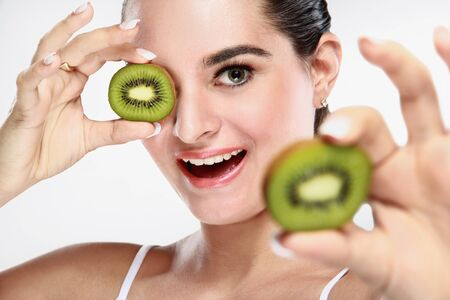 portrait of cheerful beautiful young woman with kiwi fruit in her hands photo