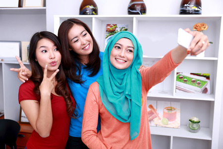 roommates: portrait of three beautiful women posing and make an expression  while taking selfie photos using mobilephone camera Stock Photo
