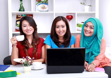 three beautiful college students smiling and studying together at livingroom Stockfoto