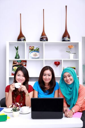 asian adult: portrait of three beautiful college students smiling and studying together at livingroom