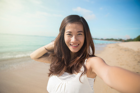 A portrait of a Happy young Asian woman take selfie, smile to camera photo