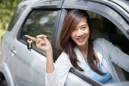 asian travel: A portrait of Young asian woman holding a key car on her finger outside the window