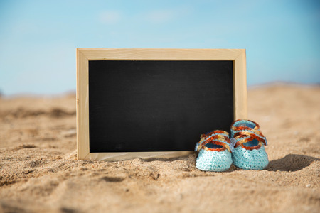 baby shoes: A portrait of a pair of blue knit toddler shoes and mini chalkbroad, sand on the beach background