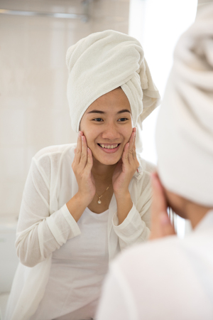 skin care face: A portrait of an Asian young woman taking care her face with both hands, smile
