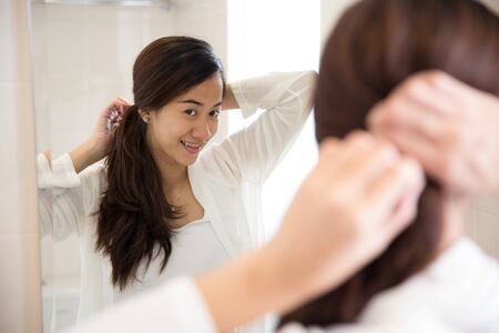 A portrait of a Beautiful asian woman tying her hair neatly in front of a mirror Stock Photo
