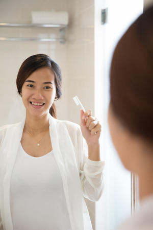 look in mirror: A portrait of an asian young woman will brushing her teeth happily
