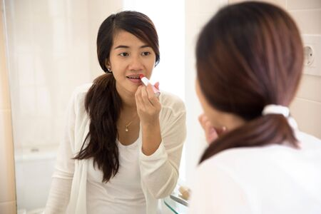 working dress: A portrait of a Beautiful asian woman putting make-up on, applying lipstick on her lips
