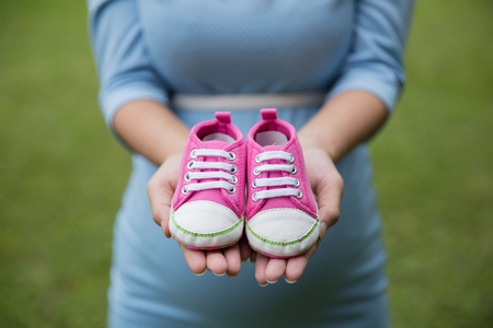 motherly: A portrait of A pair of pink toddler sneakers in the hands of pregnant woman Stock Photo