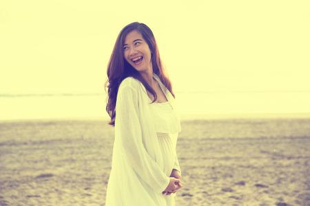 happy pregnant: Un retrato de una mujer embarazada hermosa sonrisa brillante en vestido blanco en la playa